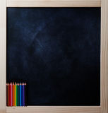 Square blackboard with colored pencils Stock Photography