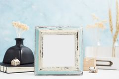 Square blue Photo frame mock up with green tropical plants in vase, ceramic star and candle on shelf. Scandinavian style