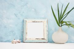 Square blue Photo frame mock up with green tropical plants in vaseand small wooden houses on shelf. Scandinavian style Royalty Free Stock Image
