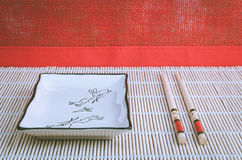 Square bowl and chopsticks. Against the background of a red wall Stock Photo