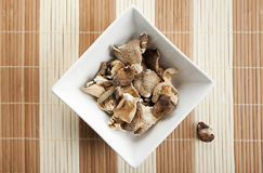 Square bowl of shitake mushroom on bamboo mat Royalty Free Stock Images