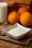 Square bowl with white yogurt on jute cloth Royalty Free Stock Images