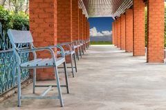 Square brick wall with many benches. Close-up image of rectangular brick wall with many benches on concrete floor which is used as exit under wooden ceiling royalty free stock photo