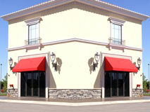 Square Building with Red Trim. Square modern office or retail shop building with red awnings as trim stock photos