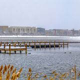 Square Buildings against sky on a snow covered landscape beyond the lake in winter. Snowy wooden decks can also be seen above the water with grasses in the stock images