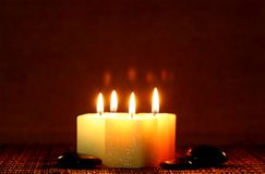 Square candle with river stone. Four square candles with black river stones Stock Photo