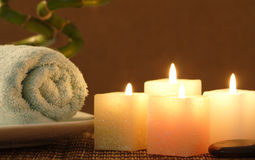 Square candle and towel before bamboo. Four square candles, blue towel before bamboo ready for spa Royalty Free Stock Images