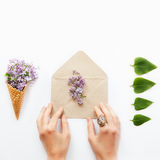 Square card with women hands touching craft paper envelope with lilac flowers surrounded by a waffle corn with a bouquet of lilac. And a row of green leafs on Royalty Free Stock Photo