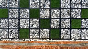 Square check pattern of grass and stone wall with wooden floor Royalty Free Stock Image