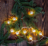 Square christmas background with string lights and fir branches on wooden planks. Stock Photo