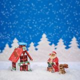 Square Christmas card with red house, Santa and Bunny and it`s snowing. Square blue Christmas card where Santa and the Bunny are outside the house with a red Royalty Free Stock Image