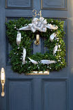 Square christmas wreath on door. Unique square christmas wreath hanging outside on door Stock Photo