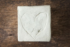 Square with clay heart on wooden surface Royalty Free Stock Photography