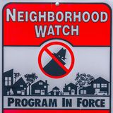 Square Close up of a Neighborhood Watch sign against a blurred background. The sign warns that all suspicious persons and activities are reported to the law royalty free stock photography