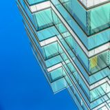 Square Close up of an office building exterior against blue sky on a sunny day. Roller blinds on the windows provide shade and privacy to the rooms royalty free stock photography