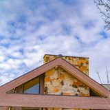 Square Close up of the roof of a house against trees and sky with cottony clouds. A colorful chimney protrudes from the roof of this house stock photography