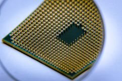 A square computer processor pulled from a broken computer. The processor is on the table. View of the contacts through a magnifyin. G glass stock image