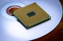 A square computer processor pulled from a broken computer. The processor is on the table. View of the contacts through a magnifyin. G glass Royalty Free Stock Images