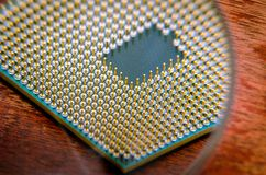 A square computer processor pulled from a broken computer. The processor is on the table. View of the contacts through a magnifyin. G glass Royalty Free Stock Image