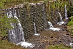 Square concrete blocks dam on the river with holes for drain wat Royalty Free Stock Images