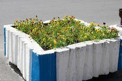 Square concrete stone old wretched ugly Soviet flower bed painted with whitewash, Russian landscape design royalty free stock photos