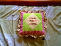 Square cushion with words Home sweet home Royalty Free Stock Image