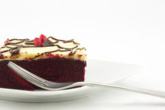 Square cut piece of red velvet cake with fork. Delicious piece of red velvet cake iced with cream cheese frosting on white plate with fork in front. Horizontal stock photography