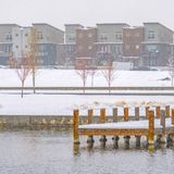 Square Deck on a lake overlooking buildings in Daybreak. Snowy wooden deck on a lake in Daybreak, Utah viewed in winter. Buildings against gloomy sky can be royalty free stock photography