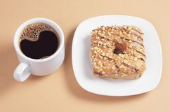 Square donut with glaze and coffee. Square donut with a caramel glaze is decorated with roasted nuts and chocolate stripes in plate and cup of coffee on a light royalty free stock image
