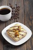 Square donut with glaze and coffee. Square donut with a creamy glaze is decorated with roasted corn and chocolate stripes and cup of coffee on the old wooden royalty free stock photography