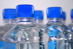 Square drinking water bottles. Closeup of group of square, plastic, drinking, water bottles with blue lids Royalty Free Stock Photos