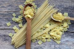 Square dry yellow pasta in a mix with long spaghetti on and near the wooden spoons royalty free stock images