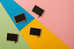 Square empty chalk board speech bubbles on colored papers Stock Photos