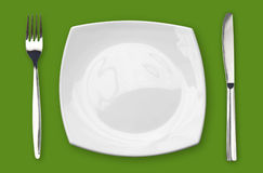 Square empty plate fork and knife on green table Stock Photography