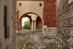 Square enclosed patio with arch and brick walls. From intrance to exit Stock Images