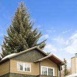 Square Exterior view of a house with balcony and snow covered roof in winter. The towering coniferous tree behind the home can be seen against cloudy blue sky stock photos