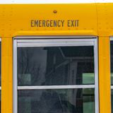 Square Exterior of a yellow school bus with a close up view of its glass window stock photography
