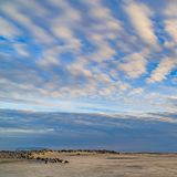 Square frame Boundless blue sky with gray and white clouds over a vast sandy shore royalty free stock image
