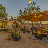 Square frame Cozy stone patio with string of lights over a covered seating and dining area. The house has a glass paned double door and window with view of the royalty free stock image