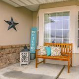 Square frame Facade of a home with a wooden bench on the welcoming front porch stock photography