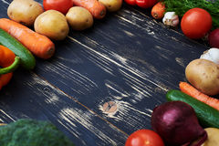 Square frame forming by organic vegetables over wooden flat layo Royalty Free Stock Image