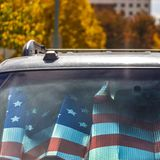 Square frame Front view of a shiny gray vehicle against lush trees on a sunny autumn day. Inside the vehicle is a sunshade with an American flag design royalty free stock photos