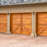 Square frame Luxurious exterior of a house with stylish brown wooden garage doors royalty free stock images
