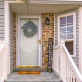 Square frame Pleasing home with stairs and half hexagon shaped window at the facade. A wreath, doormat, welcome sign, and wall lamp adorn the doorway stock photo