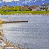 Square frame Wooden deck on a scenic lake with rocks and bright green grasses on the shore. Bridge and houses can be seen against snowy mountain and cloudy sky royalty free stock images