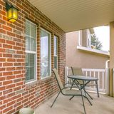Square Front porch of a home with table and chairs in front of brick wall and window. The outdoor scenery is reflected on the sidelight that flanks the green stock image