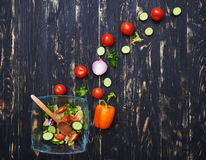 Square glass bowl with salad and ingredients arranged in arch st Stock Image