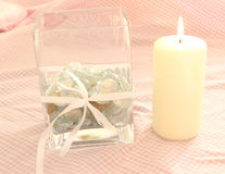Square Glass Vase And Candle. This photo shows a square glass vase filled with glass pebbles with a lit candle and on Pink gingham bachground Stock Photo