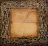 A square grapevine wreath on a wooden background royalty free stock image