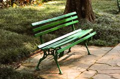 Square green bench. Green bench on a sunny day. Conversation spot. Where the spies do their meetings stock photo